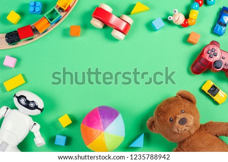Baby kids toys frame with teddy bear, toy cars, robot, colorful bricks, cubes on pink background #1235788942