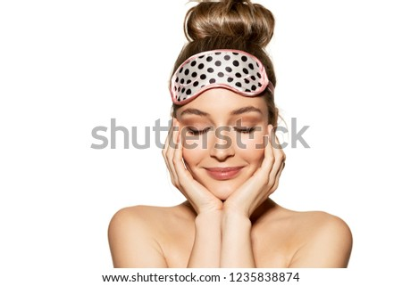 Portrait of lovely young woman wearing sleeping mask and kindly smiling. Beauty and skincare concept. Naturally beautiful girl posing on white background #1235838874
