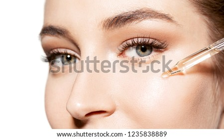 Close-up portrait of beautiful young woman with shiny perfect skin. Skincare and beauty concept. Attractive lady moisturizing face with oil on white background #1235838889