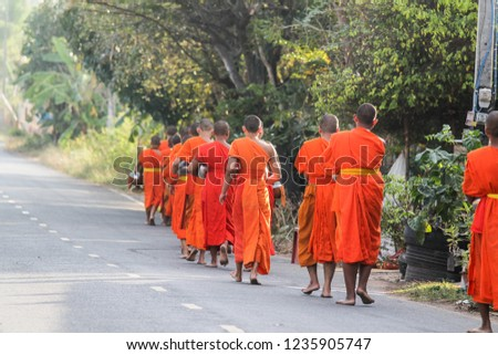 Buriram / Thailand - April 10, 2018: monk walking for receive food at morning from local people in the village. #1235905747