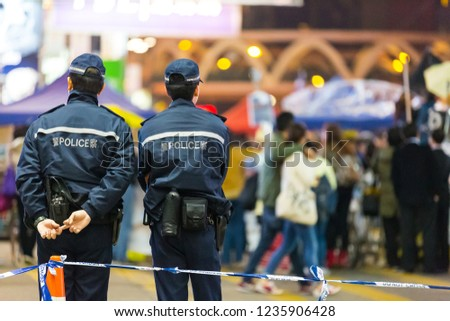 Two police keep watch crowds in front of a Police cordon line. Hong Kong.