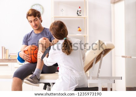 Handsome basketball player visiting female doctor traumatologist #1235973190