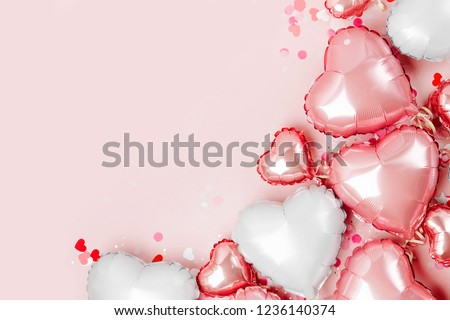 Air Balloons of heart shaped foil  on pastel pink background. Love concept. Holiday celebration. Valentine's Day or wedding/bachelorette party decoration. Metallic balloon #1236140374