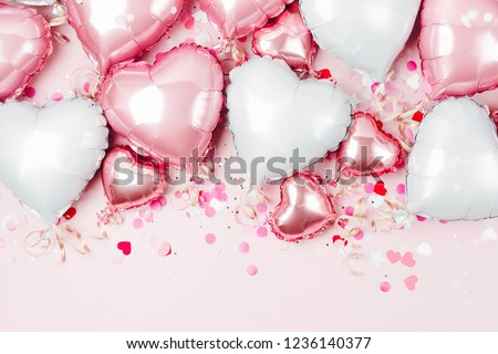 Air Balloons of heart shaped foil  on pastel pink background. Love concept. Holiday celebration. Valentine's Day or wedding/bachelorette party decoration. Metallic balloon #1236140377
