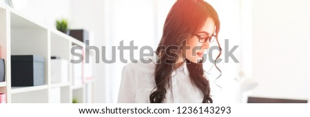 Beautiful young girl stands in the office thumbs a folder with documents. #1236143293