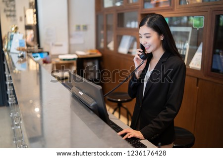 Welcome to the hotel,Happy young Asian woman hotel receptionist worker smiling standing,she taking  telephone call at a Modern luxury reception counter waiting for guests getting key card in hotel    #1236176428