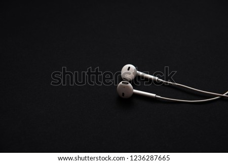 Kyiv / Ukraine - November 20, 2018: Apple headphones on a black background #1236287665