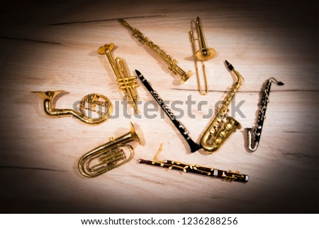 A number of toy wind instruments  lying on a wooden board, dark vignette Royalty-Free Stock Photo #1236288256