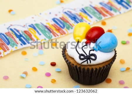 Close-up shot of a cupcake with colorful balloon shape and happy birthday sign in background.