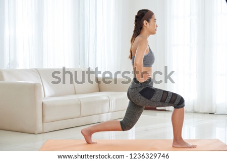 Side view of young athletic Asian woman in activewear doing lunge exercise while having workout at home #1236329746