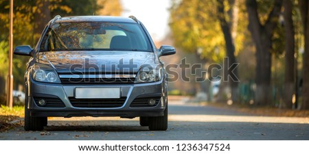 Front view of gray shiny empty car parked in quiet area on wide alley under big trees on blurred green and yellow folliage bokeh background on bright sunny day. Transportation and parking concept. Royalty-Free Stock Photo #1236347524