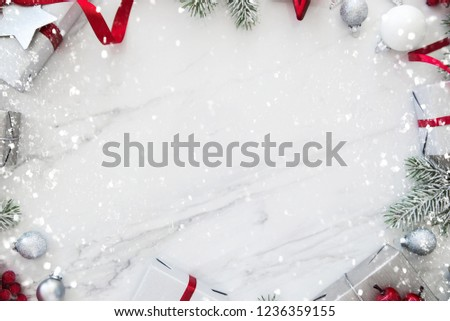 Merry Christmas and Happy Holidays greeting card, frame, banner. New Year. Red, silver Christmas gifts, presents and ornaments on white marble background top view. Winter holiday xmas theme. Noel. Fla #1236359155