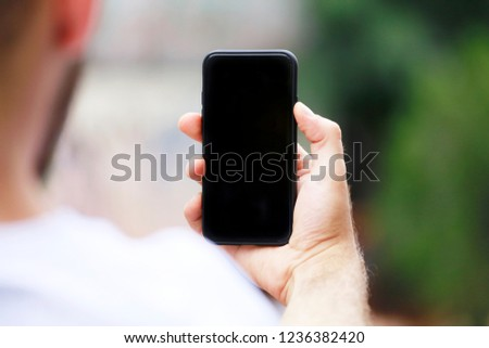 Man with smart phone on hand, blurred background. #1236382420