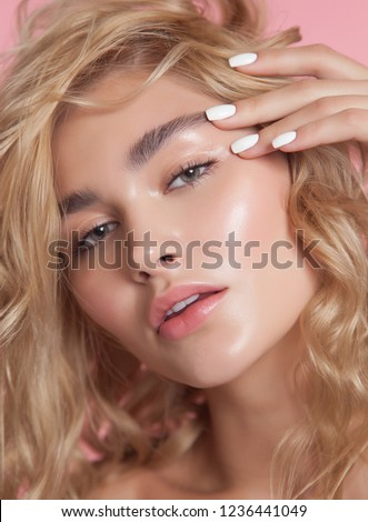 close-up beauty portrait. young model with glowing healthy skin. beautiful blonde woman with natural make-up. white nail laquer Royalty-Free Stock Photo #1236441049