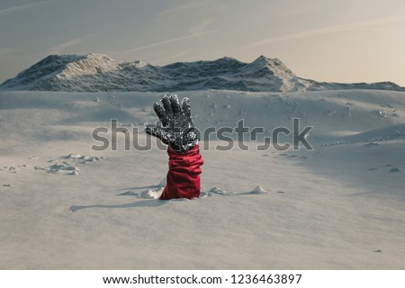 Hiker stretching out his snow covered hand to signal help because of snow avalanche . Danger extreme concept Royalty-Free Stock Photo #1236463897