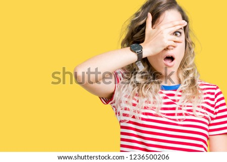 Beautiful young blonde woman over isolated background peeking in shock covering face and eyes with hand, looking through fingers with embarrassed expression. #1236500206