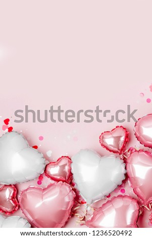 Air Balloons of heart shaped foil  on pastel pink background. Love concept. Holiday celebration. Valentine's Day or wedding/bachelorette party decoration. Metallic balloon #1236520492