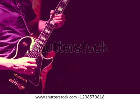 Guitarist on stage for background, soft and blur concept. Close up hand playing guitar. young musician playing guitar, live music background.Band performs on stage, rock music concert. #1236570616