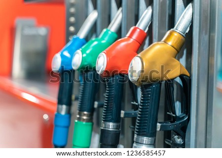Detail of a petrol pump in a petrol station.Close up on fuel nozzle in oil dispenser with gasoline and diesel in service gas station. Pattern petrol pump gun filling. Blue, green, red, golden colors. #1236585457