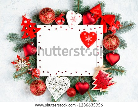 Christmas frame in the shape of a heart is surrounded by branches of a New Year tree Christmas decorations with copy space. Top view, flat lay. #1236635956
