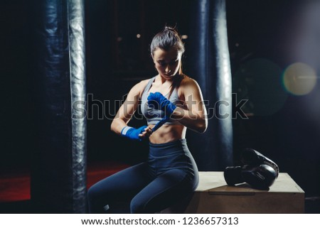 Sporty girl with strong arms prepares for tough workout, wraps bandage her fist to protect fingers, black Boxing gloves on wooden cube near. Background of punching bags #1236657313
