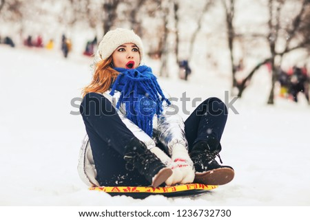 Lifestyle portrait of pretty young woman sliding down hill on snow saucer sled outdoors in winter. Funny face. Emotional photo. Winter sports with snow. Sledding - fun in the mountains. Winter fun
