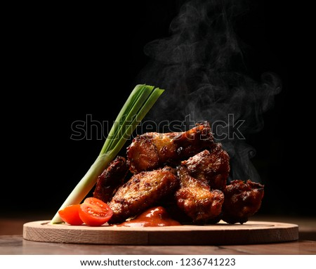 Hot and spicy bbq chicken wings with dip and hot sauce on wooden plate with steam smoke and vegetables #1236741223