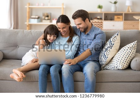 Married diverse couple and little preschool daughter sitting on couch using computer watching movie cartoons online surfing internet shopping purchasing via internet spending weekend together at home