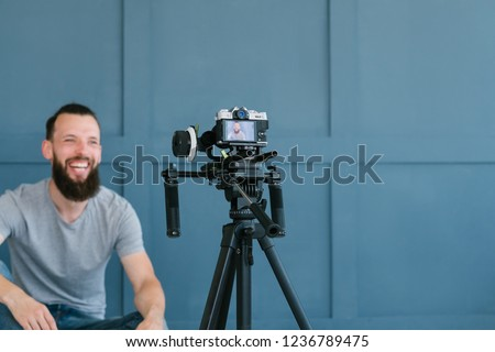content creation for social media. bearded man shooting video of himself using camera on tripod. modern technology and blogging freelance work concept. Royalty-Free Stock Photo #1236789475