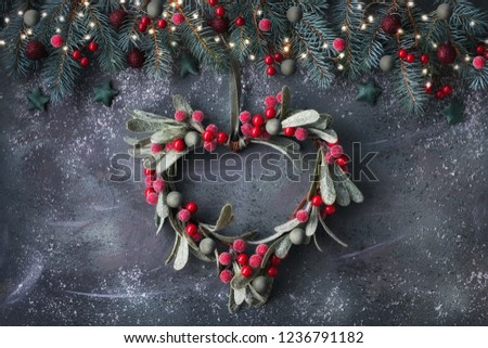 Heart-shaped mistletoe Christmas wreath and festive garland made from fir twigs, frosted berries and trinkets, on dark background
