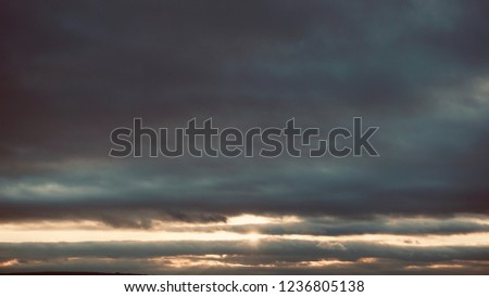 Cloudy sunset panorama. The sun trapped among the clouds in the evening horizon. Beautiful sky. Nature background.                               #1236805138