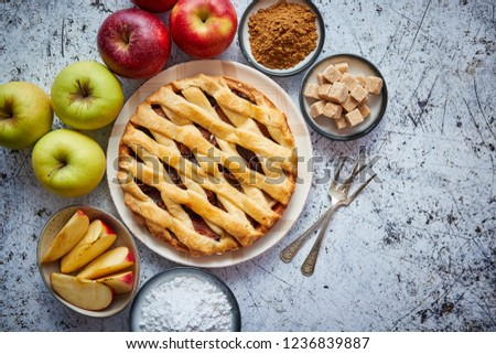 Delicious apple pie cake with a fresh red and green apples fruits, brown and powder sugar. Placed on rusty scratched stone table. #1236839887