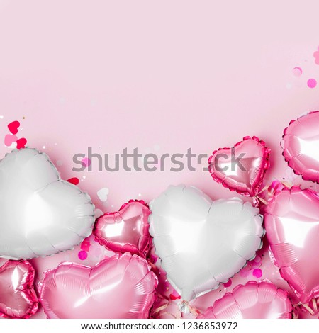 Air Balloons of heart shaped foil  on pastel pink background. Love concept. Holiday celebration. Valentine's Day or wedding/bachelorette party decoration. Metallic balloon #1236853972