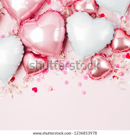 Air Balloons of heart shaped foil  on pastel pink background. Love concept. Holiday celebration. Valentine's Day or wedding/bachelorette party decoration. Metallic balloon #1236853978