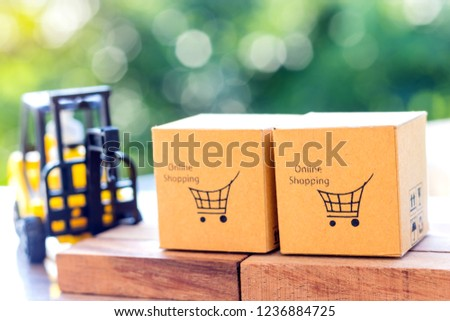 Cardboard boxes with shopping cart symbol on wooden block and mini crane truck nearby with natural background. Logistics and transportation management ideas and Industry business commercial concept. #1236884725