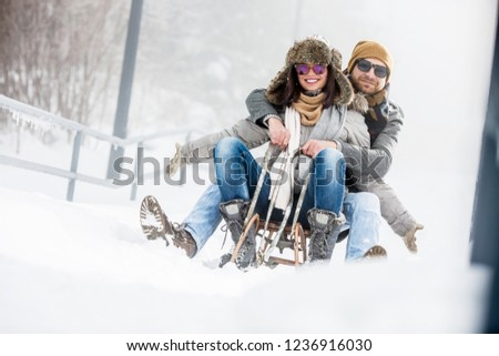 Young couple on sledge in winter outdoors
