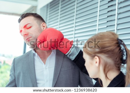 Caucasian businessman and attractive business woman with red boxing gloves punching for a fighting spirit business in corporate .Working competition business and finance concept #1236938620