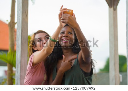 young happy and beautiful black afro American woman enjoying holidays at tropical resort with Asian girlfriend taking selfie picture with mobile phone together in women diversity race friendship