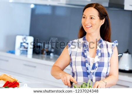 Beautiful woman standing in the kitchen #1237024348