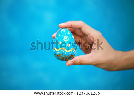 Close up of hand holding colorful painted Easter egg on blue background #1237061266