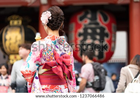 "Young girl wearing Japanese kimono standing in front of Sensoji Temple in Tokyo, Japan. Kimono is a Japanese traditional garment. The word ""kimono"", which actually means a ""thing to wear""  Royalty-Free Stock Photo #1237066486"