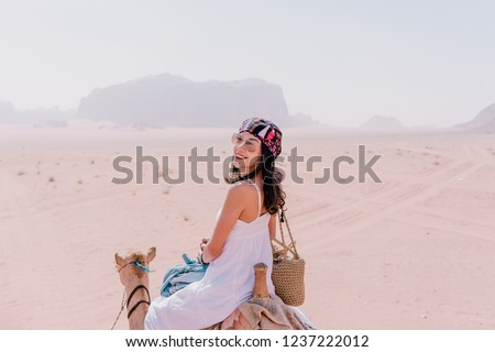 Asian young woman tourist in white dress riding on camel in wadi rum desert, Jordan #1237222012