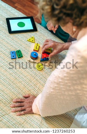 Female doctor showing geometric shape game to elderly female patient with dementia #1237260253