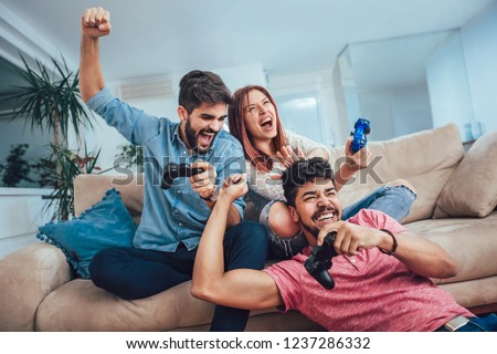 Group of young friends play video games together at home. Royalty-Free Stock Photo #1237286332