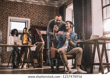 two smiling men using smartphone with multiethnic group of casual businesspeople in modern loft office behind #1237478956