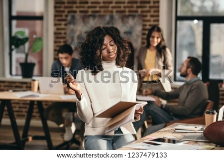 focused african american casual businesswoman holding journal with colleagues working behind in loft office #1237479133