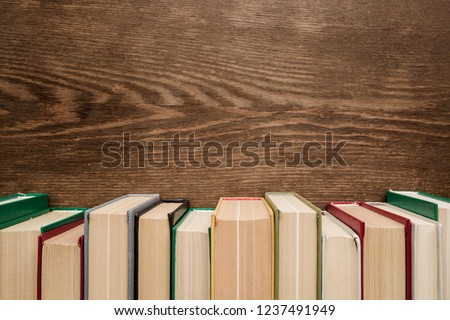 Row of old books with colorful covers on brown wooden background. Education concept. Mock up for different ideas. Empty place for text, quote or sayings. Front view. #1237491949