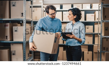Female Inventory Manager Shows Digital Tablet Information to a Worker Holding Cardboard Box, They Talk and Do Work. In the Background Stock of Parcels with Products Ready for Shipment. #1237494661