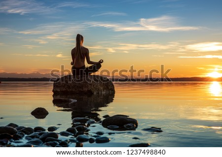 young beautiful woman girl are doing sport fitness yoga position on a stone at a beautiful lake, sea, see in the water - in the background you can see a colorful sundown - stone, water, orange sundown #1237498840