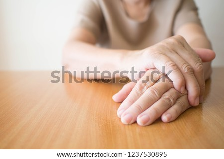 Parkinson's disease symptoms. Close up of tremor (shaking) hands of Middle-aged women patient on wooden table. Mental health and neurological disorders concept. Copy space. #1237530895